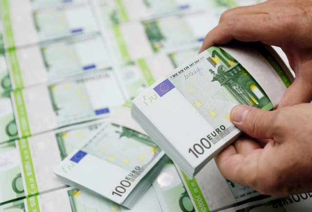 An employee checks 100 Euro banknotes at the Money Service Austria company's headquarters in Vienna